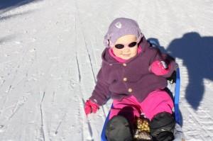 """2.Å sitte på akebrett å få kjenne på snøen, med vottene på... eller av, ja det liker Eliisa. Men best av alt... det er å suse forbi trærne mens hun kommanderer : """"Mere fart!"""" til mor og far som sørger for fremdrift i rask springmarsj."""