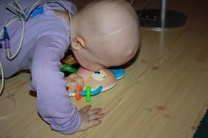 """18.Mor og Far """"maser"""" ofte om at de delvis lammede kroppsdeler må benyttes når det er sjanse for dette. Dog, Eliisa er løsningsorientert og det er enklere å trykke knappene på den nye leken med nese og munn, fremfor å benytte venstre hånda!"""