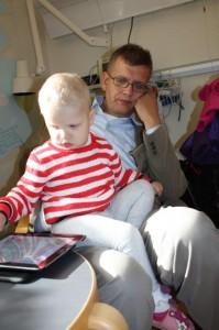 50.Et bekymret drag er å spore i fars ansikt. Mange timers søvn var det ikke blitt den siste uka. Her er vi på Riksen i forkant av at siste MR skulle bli gjennomført på Eliisa. Veslejenta lar seg heldigvis ikke affisere av foreldrenes engstelse og får ventetiden til å gå med ivrig lek på iPad.